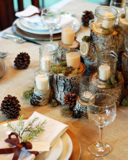 wooden logs with candles, moss and pinecones