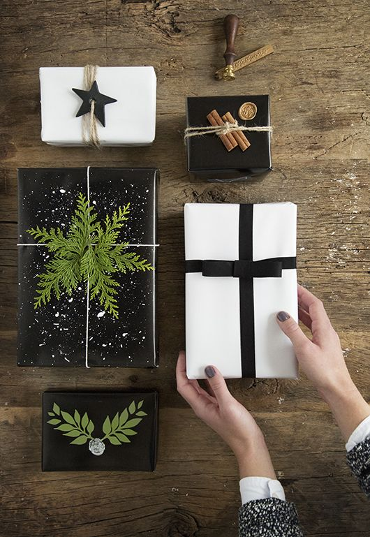 black and white wrapping paper, greenery, a clay star. cinnamon sticks and an elegant bow