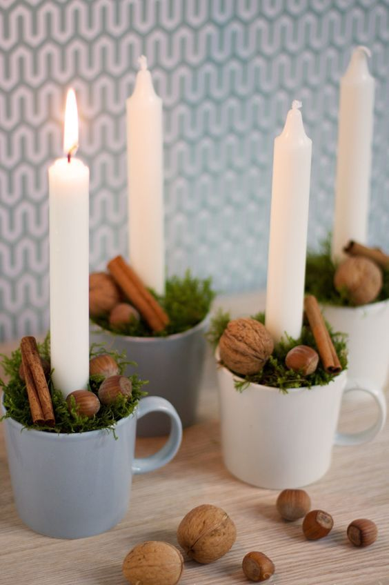cups with greenery, cinnamon sticks, nuts and candles