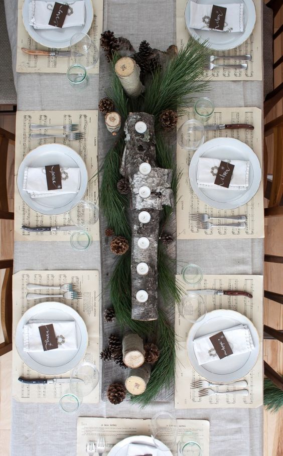 wooden plank with logs and candles, evergreens and pinecones as a table runner