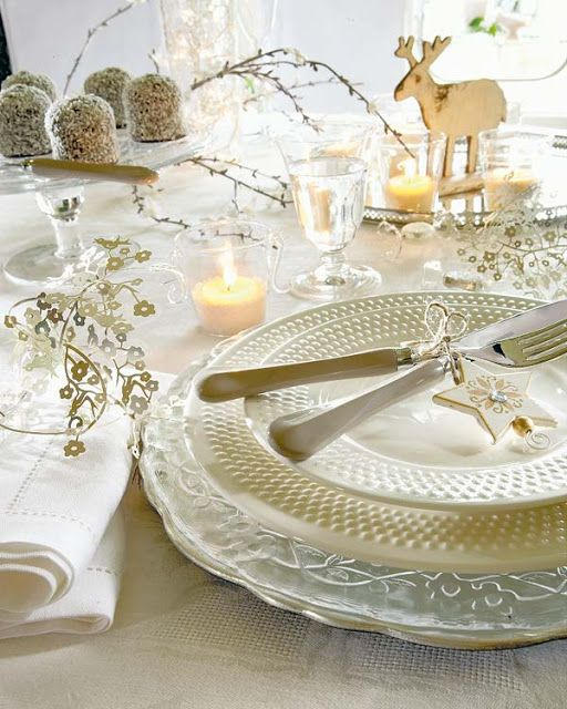 ivory Christmas table setting with wooden deer figures, branches and ornaments