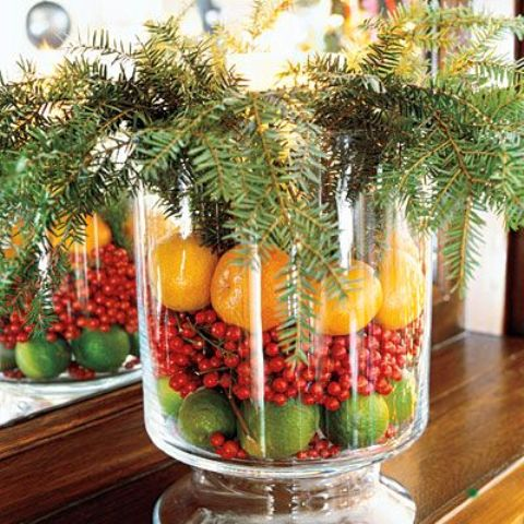 a glass bowl with limes, berries, oranges and evergreens
