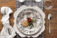 18 a plaid napkin, a patterned plate, berries and evergreens
