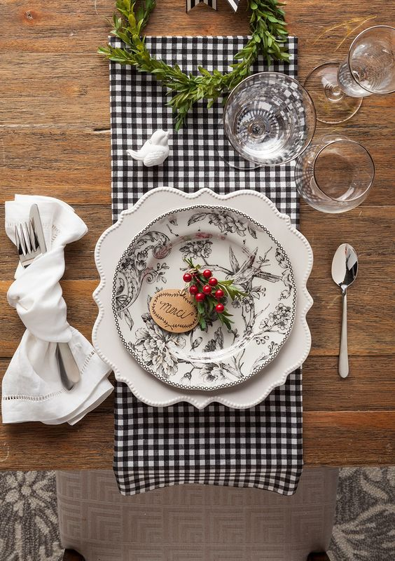 a plaid napkin, a patterned plate, berries and evergreens