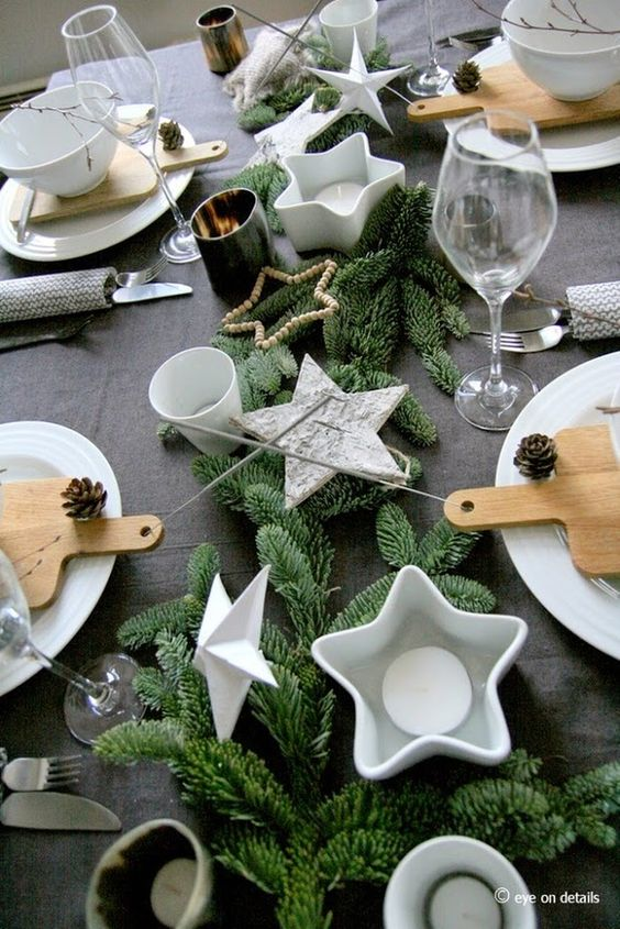 modern christmas table with a dark tablecloth, evergreens and white star candle holders