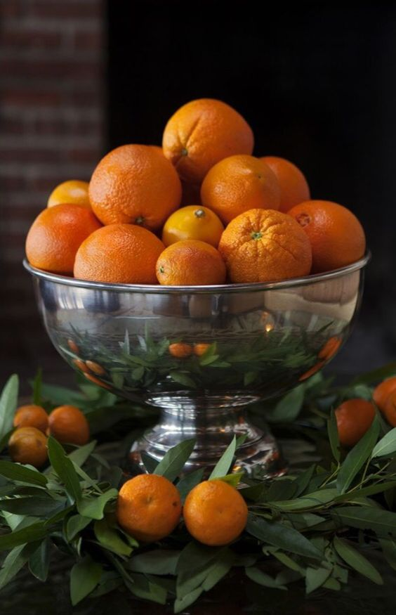 a silver punch bowl, a green wreath, and a variety of oranges to dress up your table