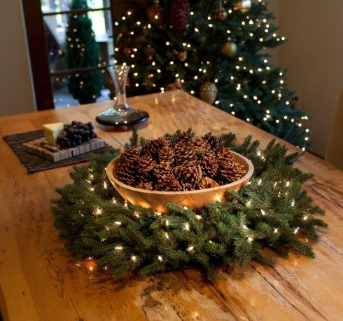 a wooden Christmas bowl with pinecones wrapped with evergreens and lights