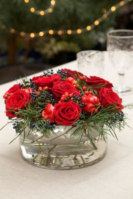 glass vessel with red roses and berries