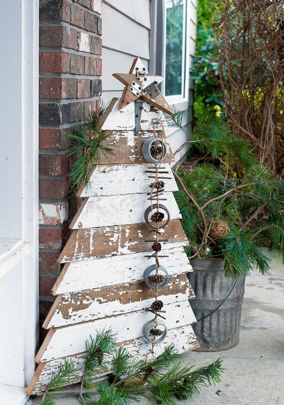 reclaimed wood Christmas tree and star in chippy white boards , with a pinecone hanging