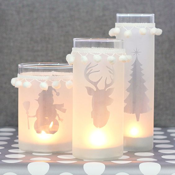 silhouette Christmas candle lanterns decorated with pompom trim
