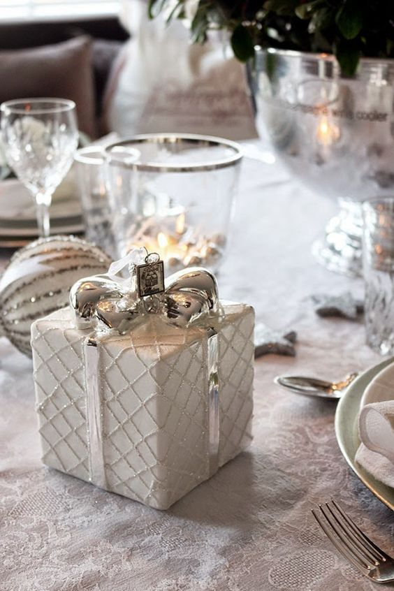 white and silver Christmas table with gift boxes and candles