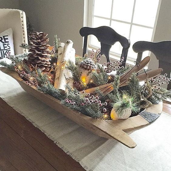 a vintage display with pinecones, berries, branches and skis