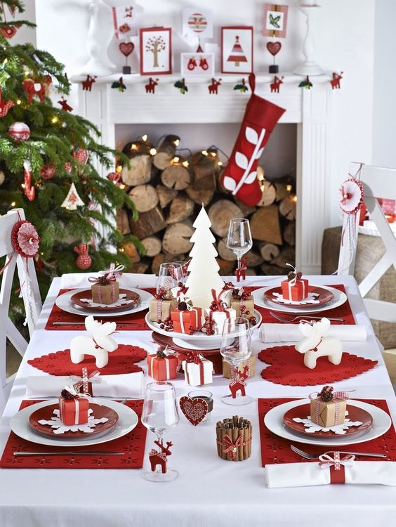 red and white tablescape with whimsy-shaped candles, gift boxes and red placemats