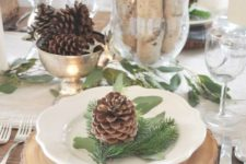 22 wood slice, a plaid napkin, pinecones and evergreens for each placemat
