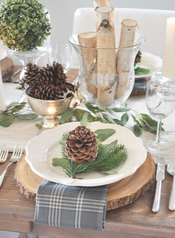 wood slice, a plaid napkin, pinecones and evergreens for each placemat