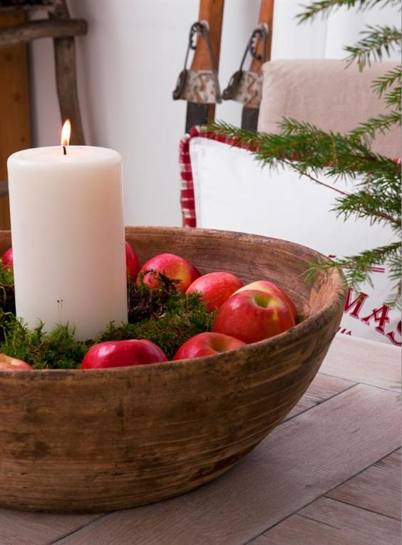 a wooden bowl with moss, apples and a pillar candle