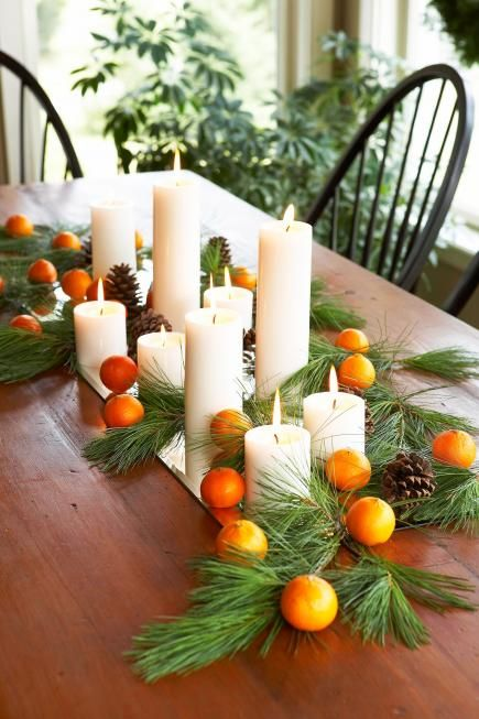 tangerines, pillar candles and evergreens on a mirror