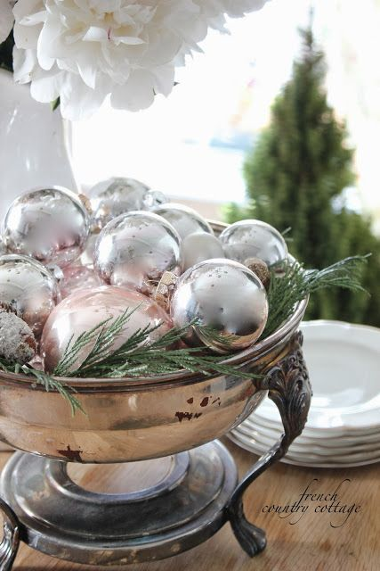 silver ornaments and fern displayed in an antique silver bowl