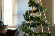 32 unique Christmas tree with a fir garland on a stand, lights and pinecones