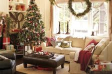 33 a large wreath for window decor and a cozy Christmas tree with red ornaments