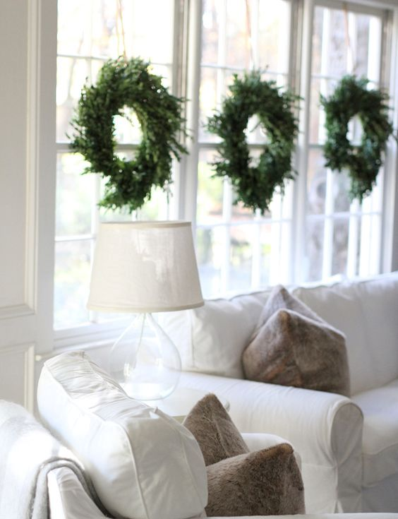 simple evergreen wreaths hanging symmetrically on the window
