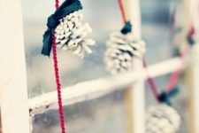 41 white pinecones on red strings for a simple and eye-catchy garland