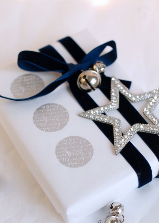 white paper, navy velvet ribbon, a silver star and jingle bells