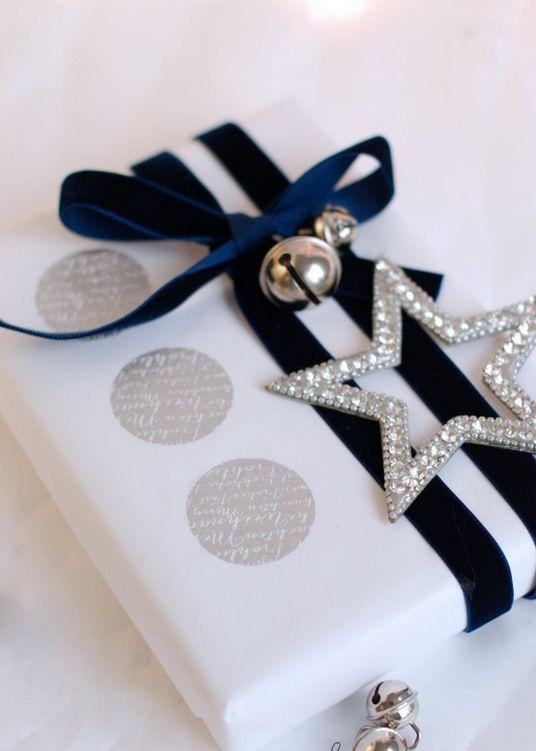 white paper, navy velvet ribbon, a silver star and jingle bells