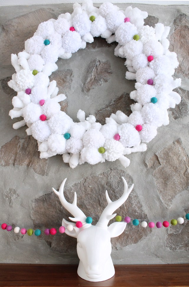DIY crispy white pompom wreath with colorful yarn balls (via tatertotsandjello.com)