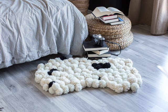 DIY large pompom rug  (via www.shelterness.com)