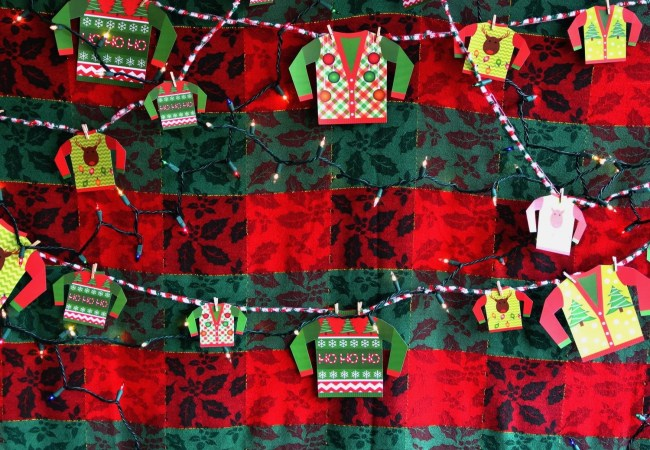create an ugly sweater booth by decorating a using a large piece of plywood and decorating it with garish wallpaper and lights