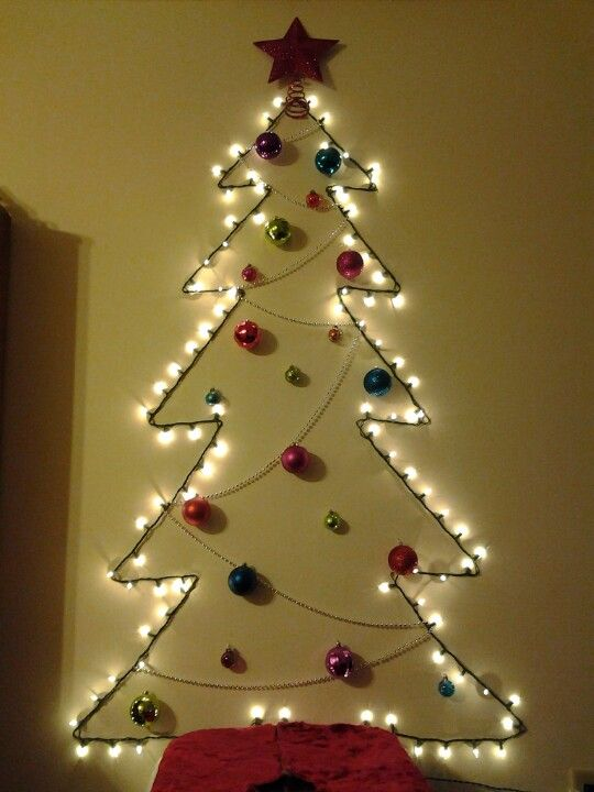 light garland tree with ornaments on the wall - 26 Wall Christmas Trees To Save The Space - Shelterness