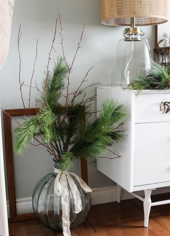 oversized round vase with evergreens and a ribbon bow