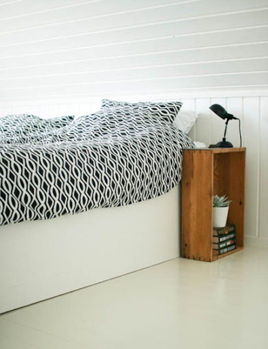 a crate placed vertically at the side of the bed