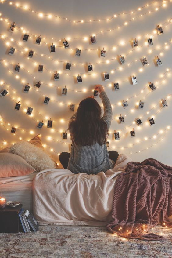 string lights over the bed and photos attached to them