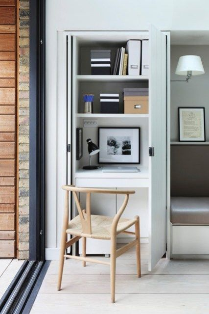 small workspace with space-saving pocket doors is concealed in a kitchen cupboard
