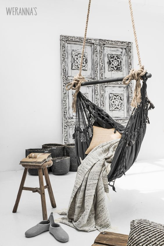 a hammock chair made of black fabric and a holder