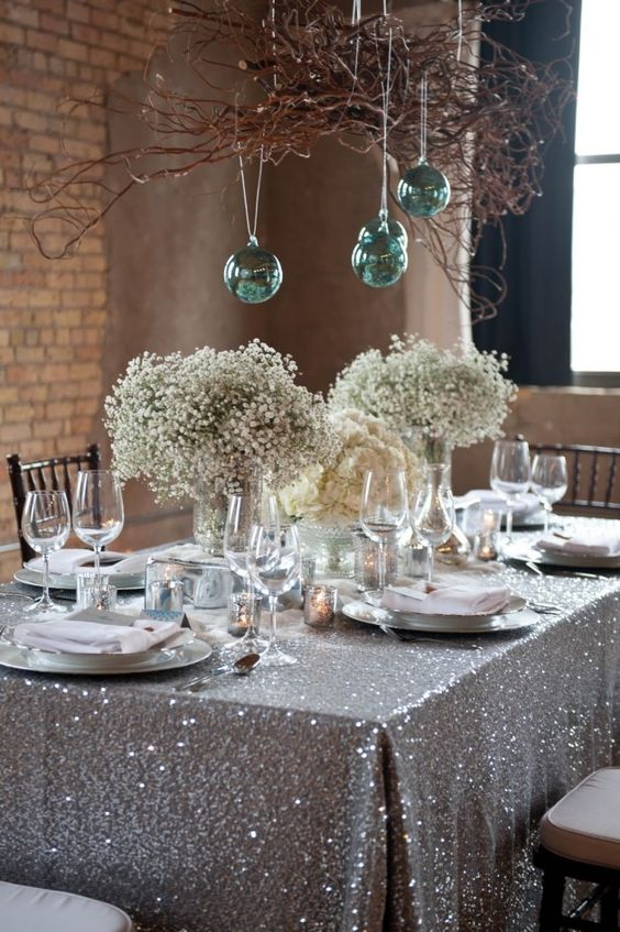 sparkling silver tablecloth and green ornaments over the table
