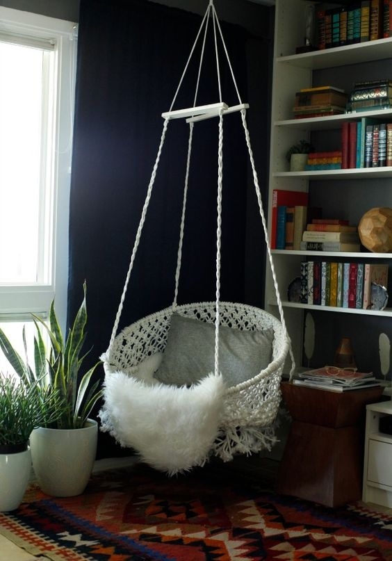 white macrame hammock chair with pillows and blankets