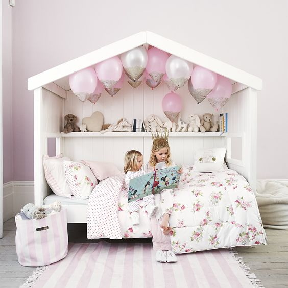 cozy house bed with pink balloons and a toy and book shelf
