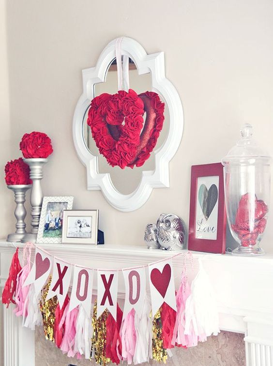 mantel decor with a heart-shaped wreath, an XO banner and sequins