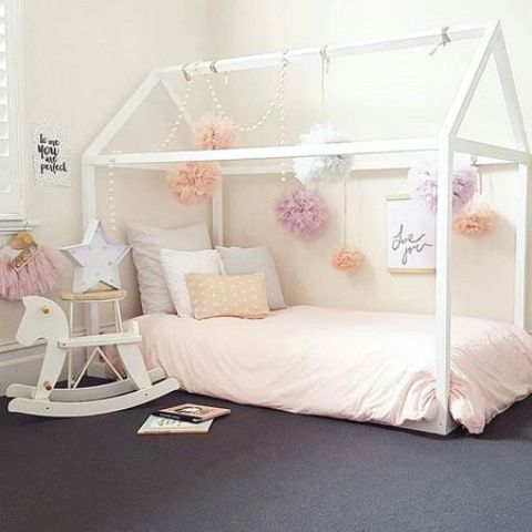 white frame house bed with pompoms hanging all over