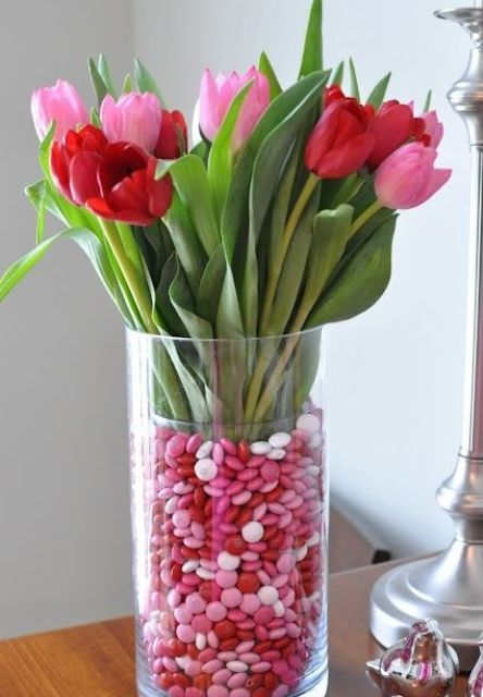 a vase filled with pink and red cnadies and flowers of the same colors