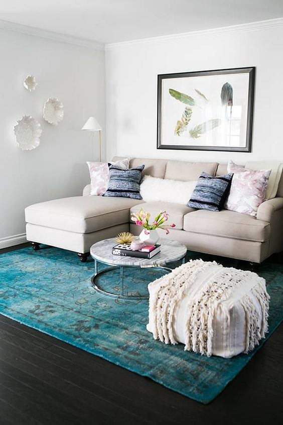 a turquoise rug is the only colorful piece here and it makes a statement