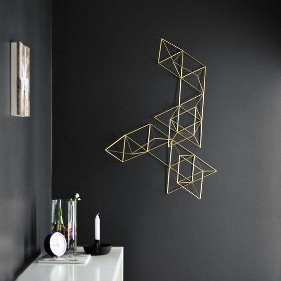 minimalist geometric 3D wall art stands out on a black wall