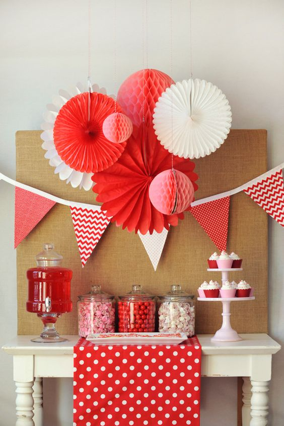 red and white paper fans and spheres are great for galentine's party decor