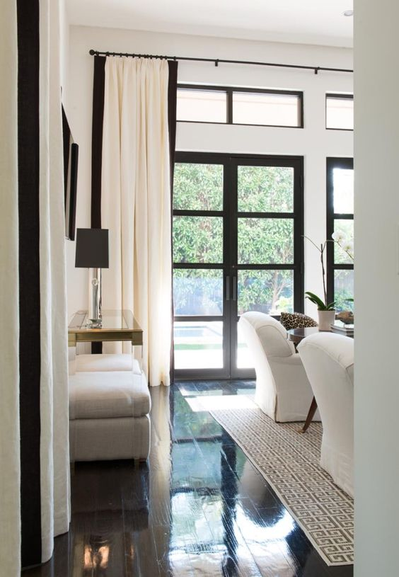 black and creamy draperies over the windows and doors