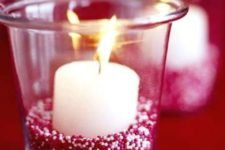 09 glass candle holder filled with red and white beads and a candle