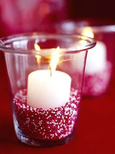 glass candle holder filled with red and white beads and a candle