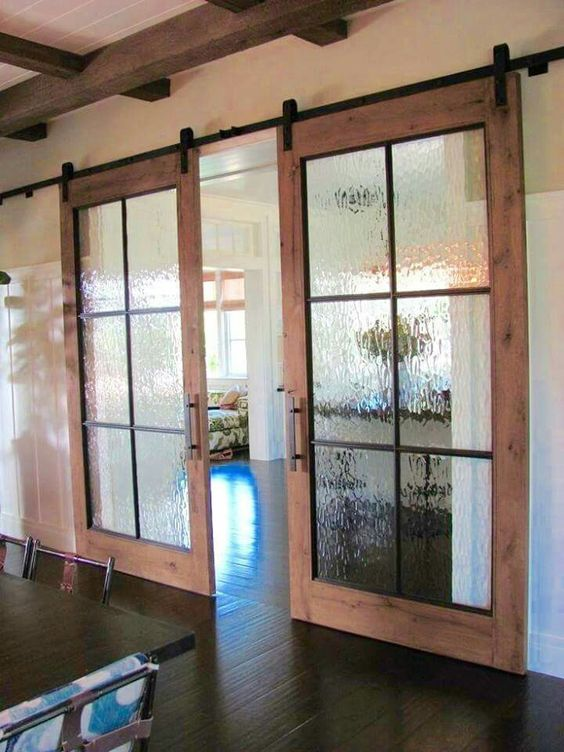 sliding barn wood doors with rain glass to separate the spaces better